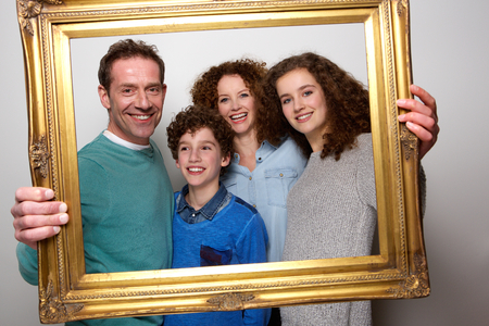 pictures: Portrait of a happy family holding picture frame and smiling Stock Photo