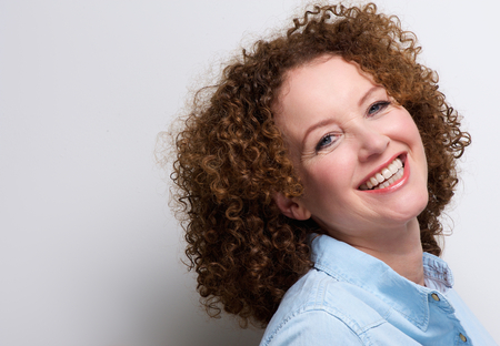 mid adults: Close up portrait of an attractive middle aged woman smiling against white background