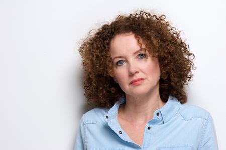 serious woman: Close up portrait of an attractive older woman with curly hair posing against white background