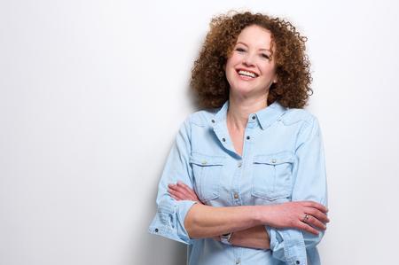 hair curly: Retrato de una mujer segura de mayor sonriendo con los brazos cruzados Foto de archivo