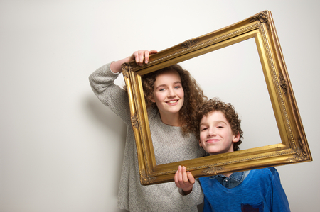 Portrait of a happy brother and sister holding picture frame photo