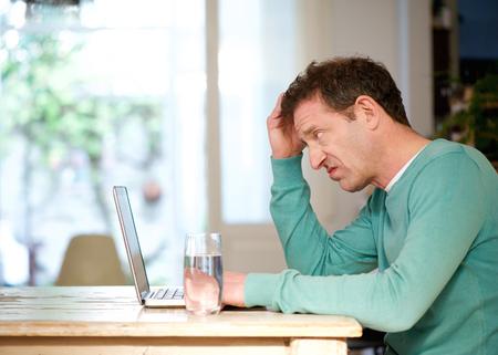 Zij portret van een verwarde man met behulp van laptop thuis