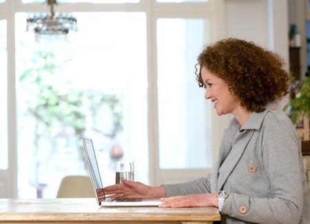 mujeres maduras: Retrato de una mujer feliz sentado en el escritorio usando la computadora port�til en casa Foto de archivo