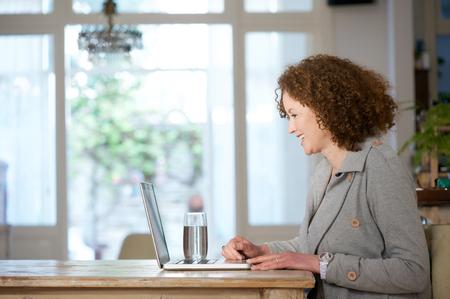 Retrato lateral de una mujer mayor que sonríe y que usa la computadora portátil en casa Foto de archivo - 39004189