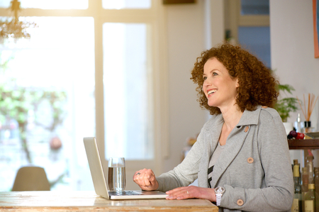 woman sitting with laptop: Side portrait of a happy middle aged woman using laptop at home Stock Photo