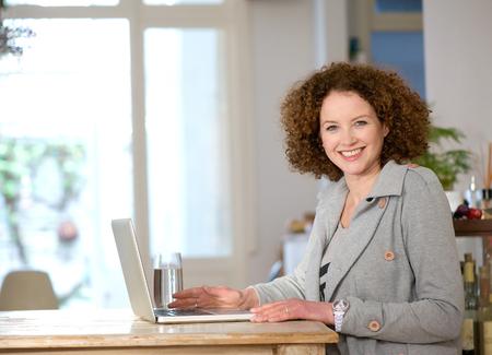 mujeres mayores: Retrato de una mujer de mediana edad feliz utilizando el portátil en casa