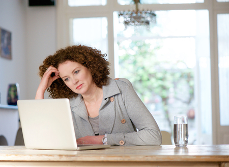 Portrait of an attractive older woman looking at laptop at home Imagens