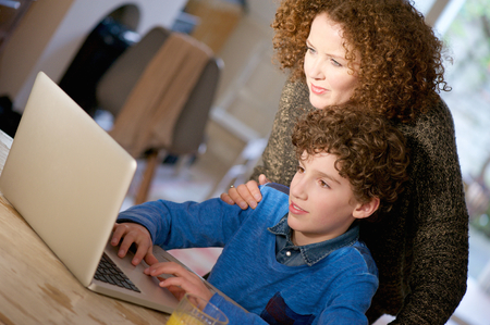 use computer: Portrait of a mother helping her son use computer at home Stock Photo