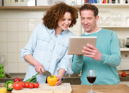 Portrait of a happy man and woman looking at tablet in the kitchen photo