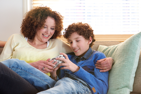 adult child: Portrait of a loving mother sitting with her son at home looking at game he is playing on mobile device Stock Photo
