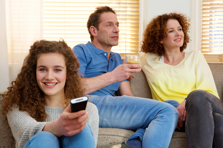 Portrait of a happy girl holding television remote control with parents in background photo