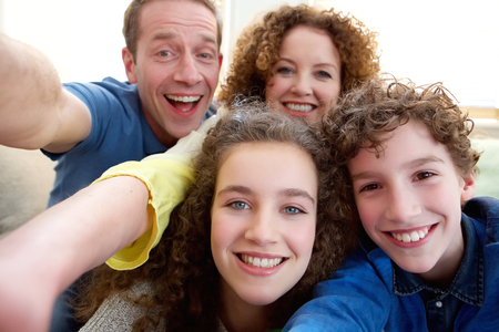 family indoors: Portrait of a happy family taking a selfie together