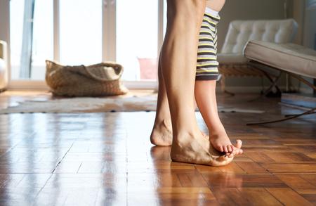 pies bonitos: Retrato de una madre caminando en casa con los niños se coloca en sus pies