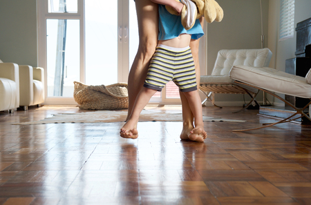 bare foot: Mother and little boy playful walking at home Stock Photo
