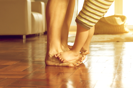 bare feet boys: Portrait of a mother and her son standing on wooden floor at home Stock Photo