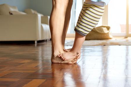 jolie pieds: Petit gar�on debout sur les pieds de la m�re � la maison