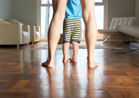 Mother and little boy feet standing on wood floor at home