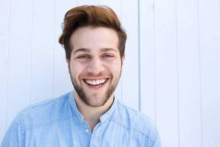 cute man: Close up portrait of a cheerful young man laughing against white