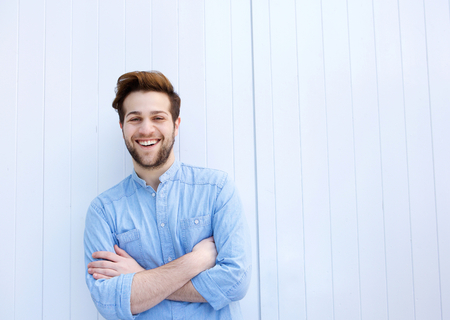 Portrait of an attractive young man smiling with arms crossed