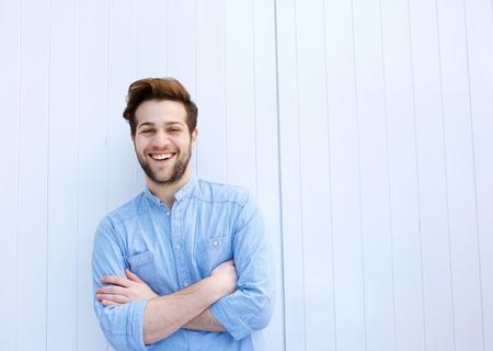 Retrato de un joven atractivo sonriendo con los brazos cruzados Foto de archivo