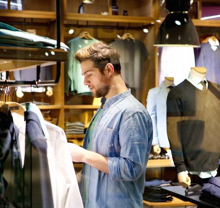 ショップで服を買いにハンサムな若い男の肖像