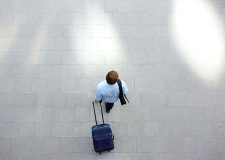 Portrait von oben von einem jungen Mann zu Fuß mit Gepäck am Bahnhof