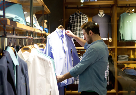 casual clothes: Retrato de un hombre joven de compras para la ropa en la tienda Foto de archivo