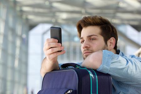 sad look: Close up retrato de un hombre que viaja joven que espera en la estación y mirando el teléfono móvil