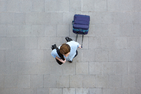 Portrait from above of a young man walking with luggage at airport