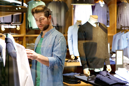 casual clothing: Portrait of a young man looking at clothes to buy at shop Stock Photo