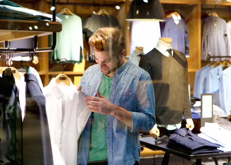 boutique: Portrait of a happy man shopping for clothes at clothing store