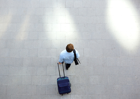 city people: Portrait from above of a young man walking with luggage at station