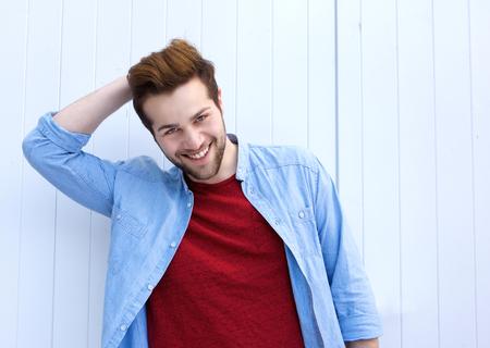 Close-up portret van een knappe jonge moderne man lachend met de hand in het haar