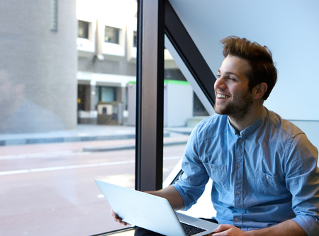 relaxed man: Candid portrait of a smiling young man using laptop