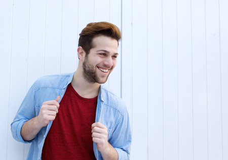 male fashion: Portrait of a cool male fashion model smiling against white