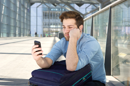 man waiting: Portrait of a young man waiting at airport with bored expression on face