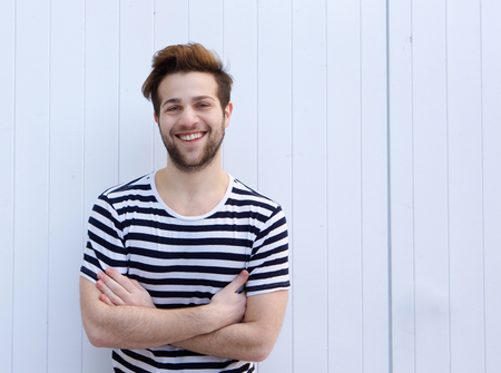 cute guy: Portrait of a cute guy smiling with arms crossed on white  Stock Photo