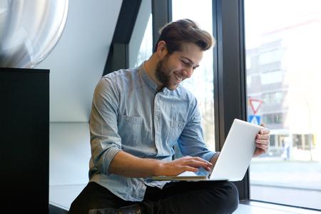 hombres jovenes: Retrato de un hombre sonriente con ordenador portátil