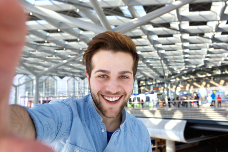a young man: Portrait of a happy man with beard taking selfie