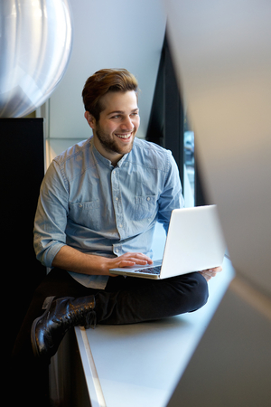 sitting man: Portrait of a happy relaxed man using laptop Stock Photo