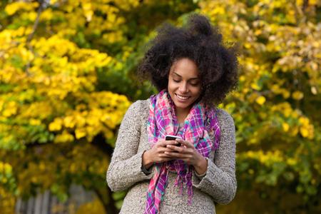 persone nere: Ritratto di un giovane messaggio di testo donna felice lettura su cellulare Archivio Fotografico