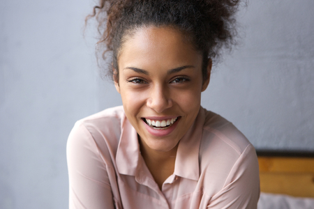 happy african woman: Close up portrait of a happy young african american woman laughing Stock Photo