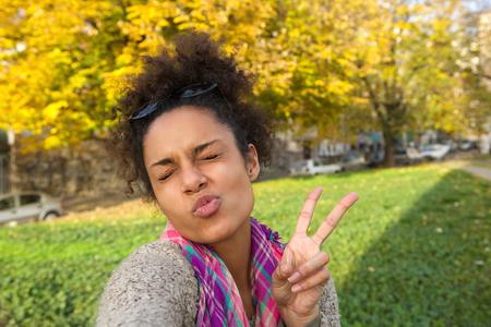 simbolo della pace: Selfie ritratto di una ragazza carina che fa fronte con il segno della pace
