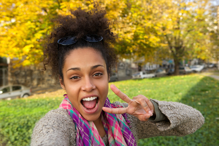 Selfie portrait of a happy woman with showing peace sign