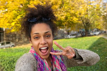 Selfie portret van een gelukkige vrouw met het tonen van vrede teken