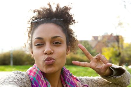 Selfie Portrait von einem hübschen Mädchen, das lustiges Gesicht mit Friedenszeichen