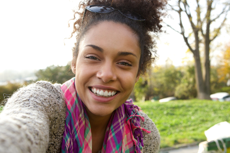 fall fun: Selfie portrait of a smiling young woman happy to be outdoors