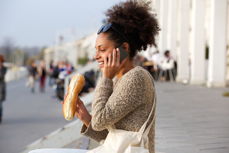 food woman: Portrait of a happy woman eating and talking on mobile phone