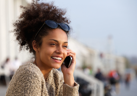 Close up portrait of an attractive young woman smiling and talking on mobile phone