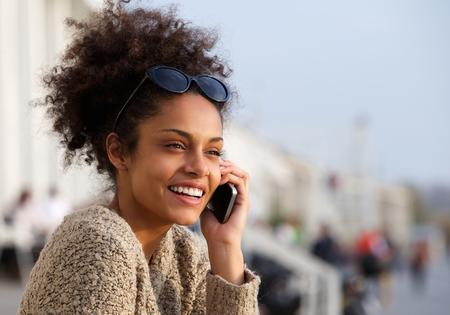 hablando por celular: Close up retrato de una atractiva mujer joven sonriente y hablando por teléfono móvil